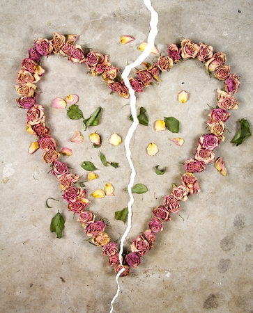 a broken heart made with old dried up flowers on a cold cracked concrete floor photo