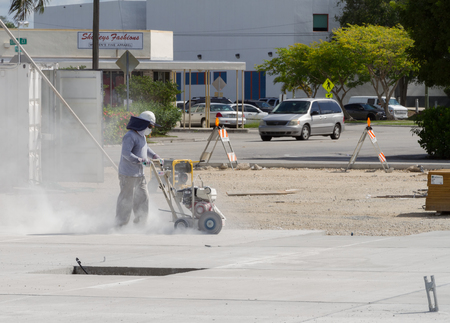 pavement: Homestead, FLORIDA - August 04, 2015: Construction worker working with a circular saw cutting stones and marble on a commercial construction site downtown Homestead, Florida