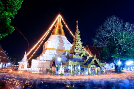 Lampang, Thailand.- Feb 25, 2012: Walking with lighted candles in hand around a temple candle light trail of Buddhism Ceremony at temple ruin on Magha Puja Day.