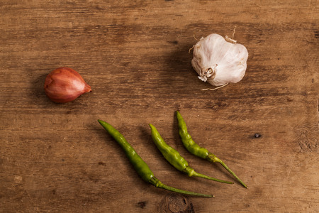 alliaceae: fresh Onions and garlic and Chili on a wooden background.