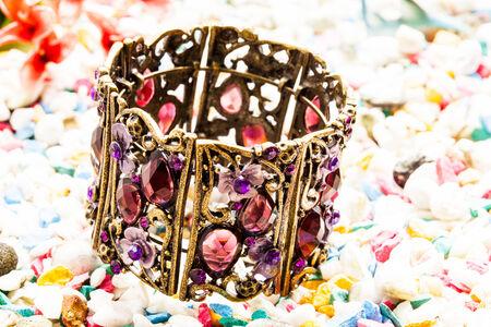 Gems bracelets on stone background. Stock Photo