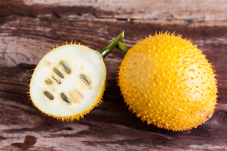bitter fruit: Gac,Baby Jackfruit Spiny Bitter Gourd, Sweet Gourd.A Southeast Asian fruit isolate on wood. Stock Photo