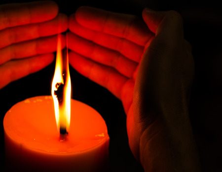 hands holding a burning candle. photo