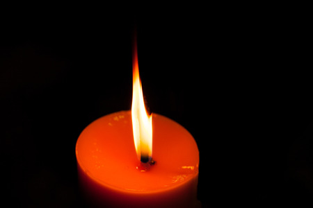 A burning candle in dark photo