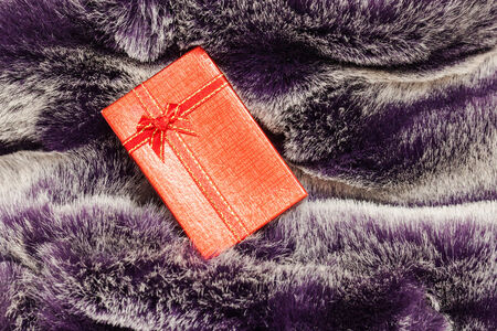 Red gift box on wool texture. photo