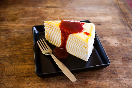 multi layered: crepe cake with strawberry jam on wooden table.