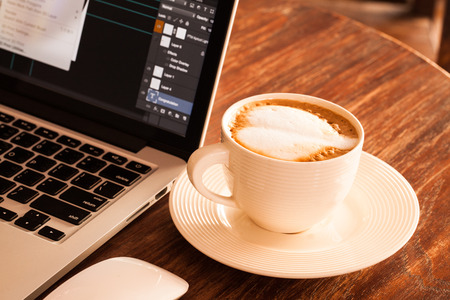 white coffee: Hot latte coffee cup in a white cup on a table laptob in coffee shop. Stock Photo