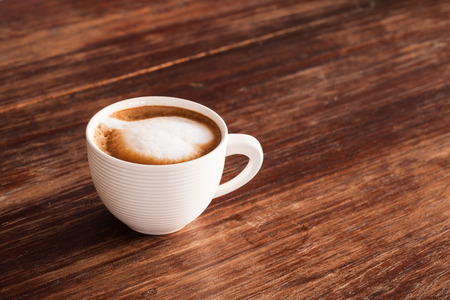 frothy: A cup of hot latte  coffee  on a wooden table.