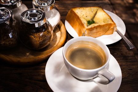 black americano coffee and garlic bread on the table. photo