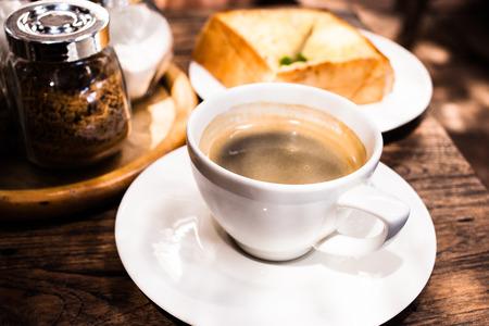 americano: black americano coffee and garlic bread on the table. Stock Photo
