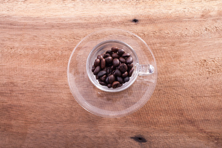 Coffee beans and bamboo spoon on wooden background. photo