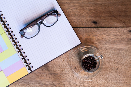 coffee cup on the table with diary and glasses. photo