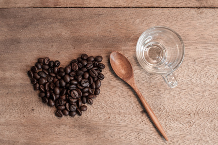 Coffee beans and bamboo spoon on wooden background. Stock Photo