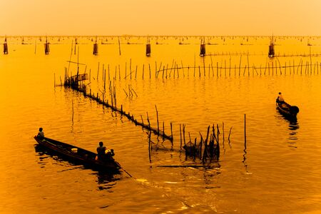 tier: Silhouette of fishermen with tier boats fishing in the lake. Editorial