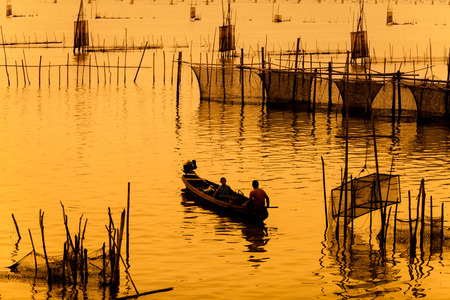 tier: silhouette of fishermen with tier boats fishing in the lake.