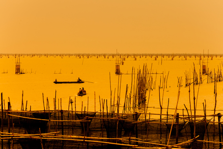 thier: silhouette of fishermen with thier boats fishing in the lake.