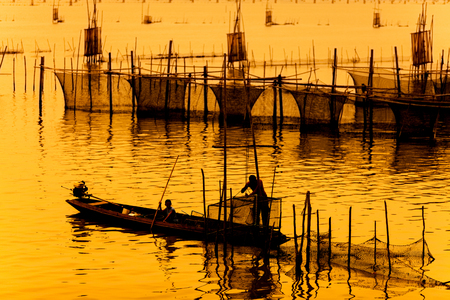 silhouette of fishermen with thier boats fishing in the lake.