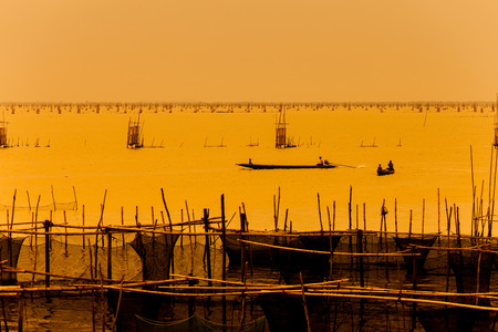 indian style sitting: silhouette of fishermen with thier boats fishing in the lake.