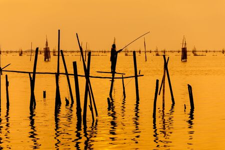 indian style sitting: silhouette of fishermen with fishing in the lake. Stock Photo