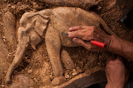 engraver: The close up carver or engraver are doing handicraft wooden elephant.