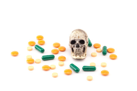 death and dying: Human skull and drugs on isolated white background. Stock Photo