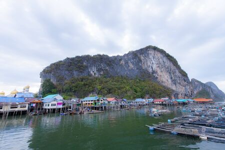 koh panyee island fisherman village settlement built on stilts of Phang Nga Bay on blue sky at noon day, Thailand