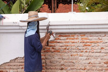 penetrate: Builders are using a chisel and hammer to punch a brick wall, cement plaster falls off. Stock Photo