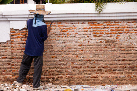 Builders are using a chisel and hammer to punch a brick wall, cement plaster falls off. Stock Photo