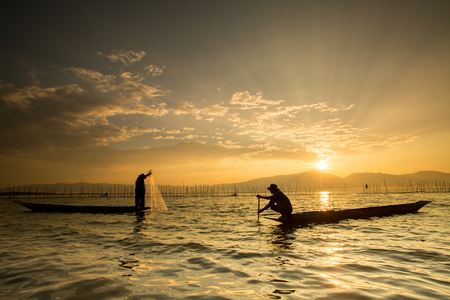 fisherman: Silhouettes of the traditional fishermen throwing fishing net during sunrise, Thailand