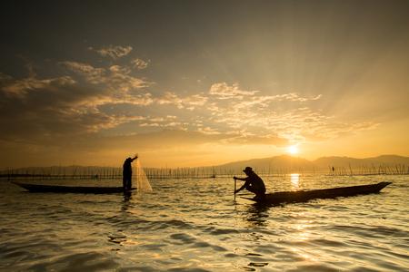 pescador: Siluetas de los pescadores tradicionales lanzar una red de pesca durante el amanecer, Tailandia