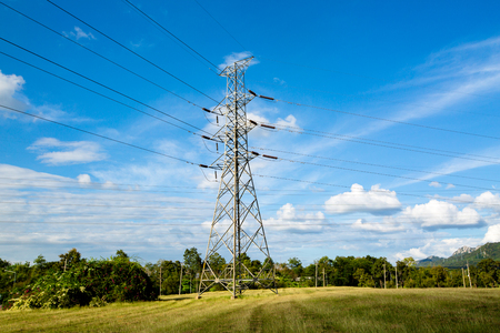 electric power: High voltage lines and power pylons in a flat and green agricultural landscape with cirrus clouds on blue sky, Mea Moh, Lampang, Thailand.