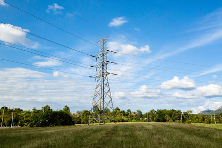 mea: High voltage lines and power pylons in a flat and green agricultural landscape with cirrus clouds on blue sky, Mea Moh, Lampang, Thailand.