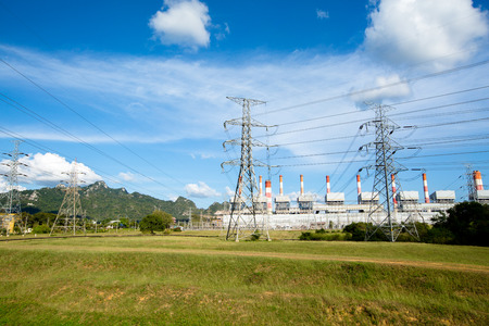 green power: High voltage lines and power pylons in a flat and green agricultural landscape with cirrus clouds on blue sky, at Mae Moh coal-fired power plant, Lampang, Thailand.