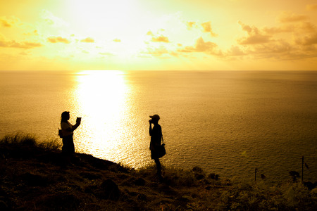 photo story: Silhouette of Couple Friends at Prom Thep Cape the Best in Phuket South of Thailand. Stock Photo
