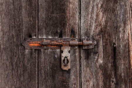 door bolt: dusty bolt on grungy old wooden door. Stock Photo