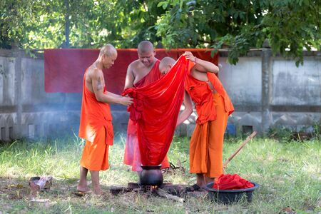 bark carving: Yasothon, Thailand. 31 Aug 2016 : The buddhist monk robe dye is allowed to be obtained from six kinds of substances: roots and tubers, plants, bark, leaves, flowers and fruits. They should be boiled in water for a long time to get the dun dye.