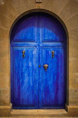 Weathered blue wooden door with golden knocker and handels photo