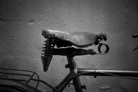 Old bike saddle in front of a wall taken from the side Stock Photo