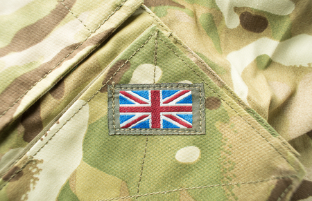 Union Jack  Union flag badge on a camouflage British army uniform. Text  writing space surrounding badge.