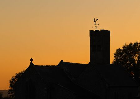 Church at sunset. Silhouette of a black bird landing on a church weathervane at sunset
