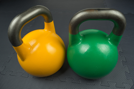 Yellow and green competition kettlebells on a fitness studio gym floor