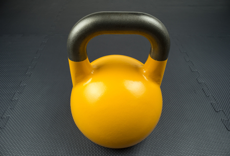 Yellow 16kg competition kettlebell on a fitness studio gym floor with rubber tiles. Potential text space at center of kettlebell.