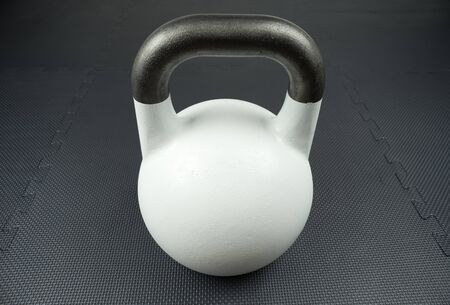 White 10kg competition kettlebell on a fitness studio gym floor with rubber tiles. Potential text space at center of kettlebell.