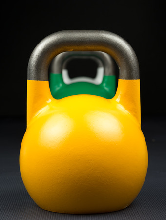 Yellow, green and white competition kettlebells lined up in a row on a weight training gym floor. Yellow competition kettlebells weigh 16kg. Green kettlebells weigh 24kg. White kettlebells weigh 10kg. Reklamní fotografie