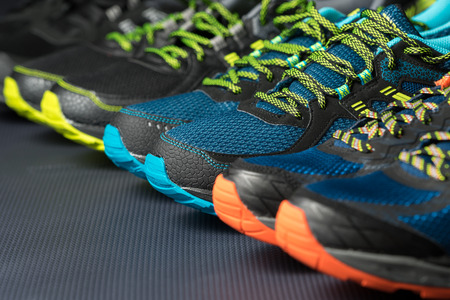 Three pairs of exercise trainers  running shoes lined up in a row on a gym floor with text  writing space