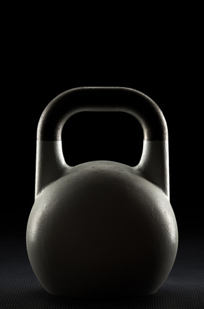 Backlit competition kettlebell silhouette on a fitness studio gym floor with potential text  writing  copy space on and above kettlebell