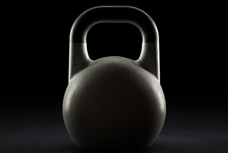 Rim lit white competition kettlebell silhouette on a fitness studio gym floor with potential text  writing  copy space on kettlebell Reklamní fotografie