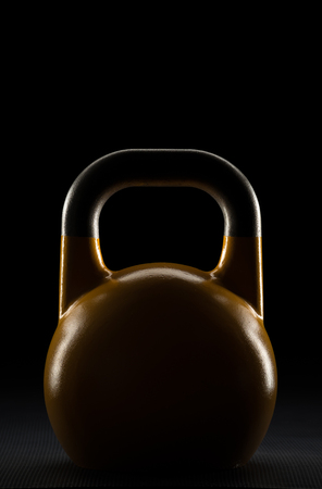 Backlit yellow competition kettlebell silhouette on a gym floor with potential text  writing  copy space on and above kettlebell