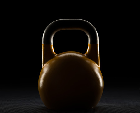 Rim lit competition kettlebell weight silhouette on a fitness studio gym floor with potential text  writing  copy space on and above kettlebell