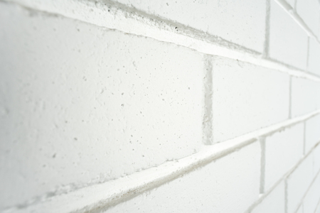 White painted brick wall at an angle. Potential use as a background with copy space on individual bricks.